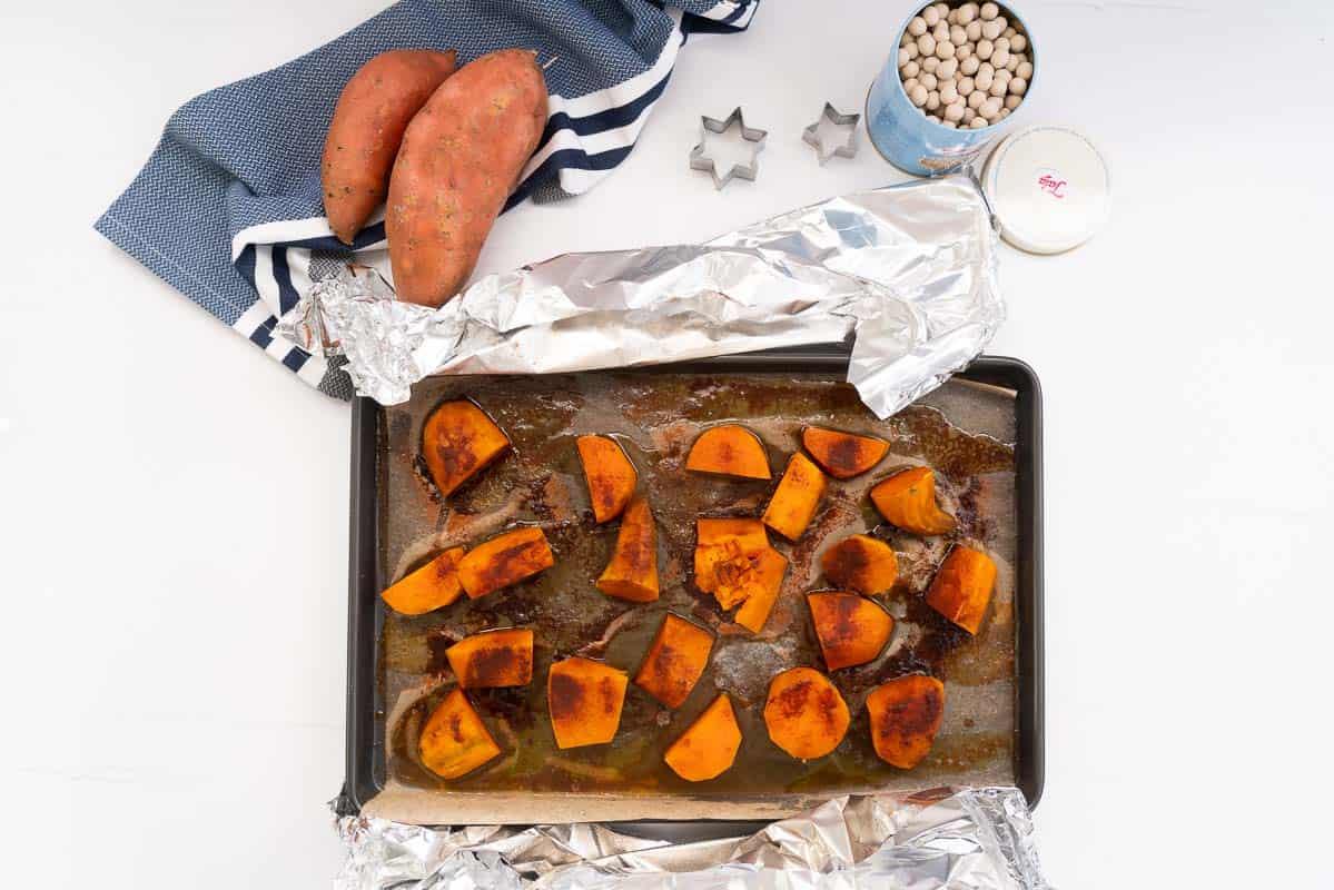 Roasted and caramelised chunks of kumara in a roasting tray.