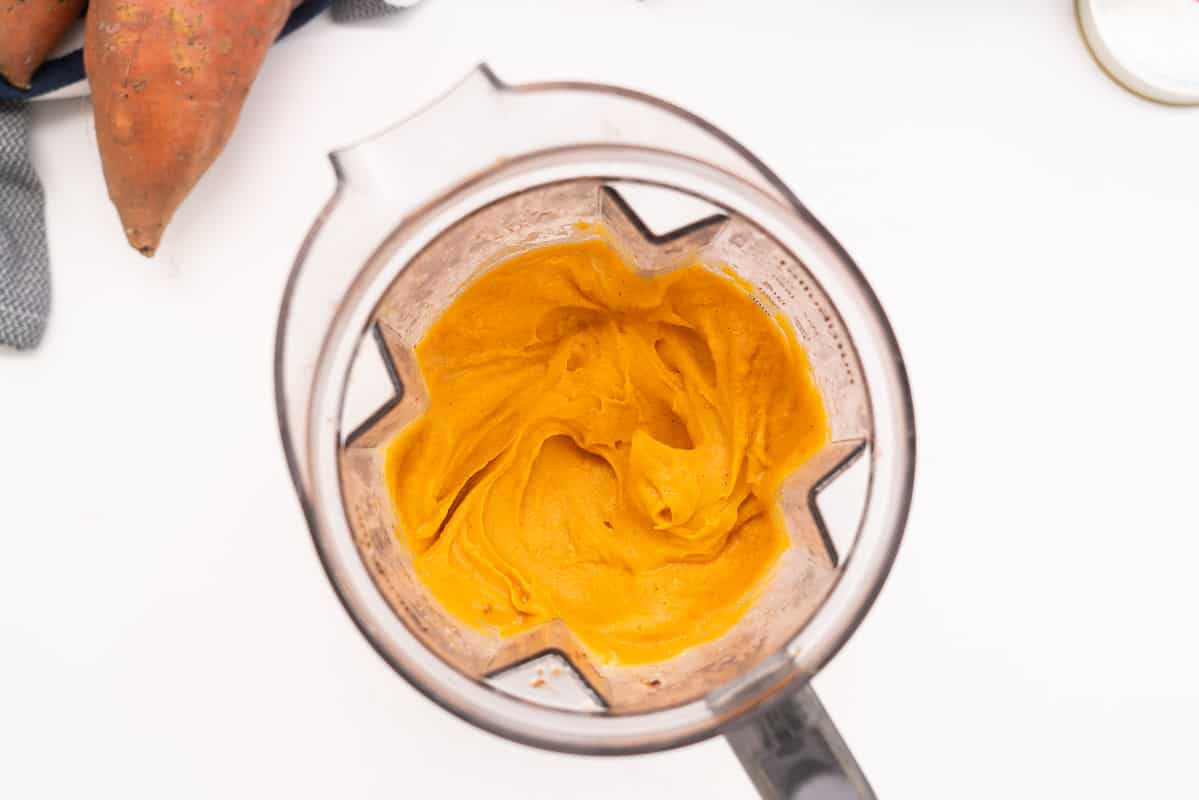 A blender jug filled with smooth sweet potato purée.