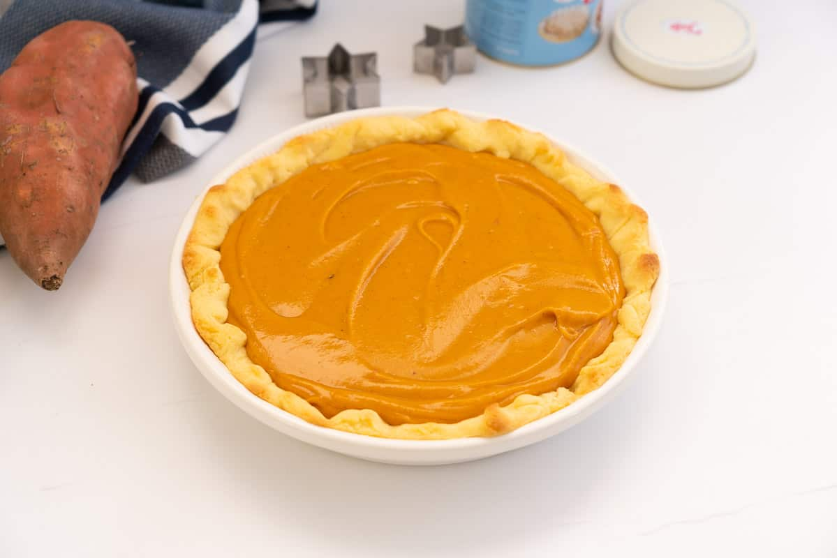 A pie crust filled with smooth sweet potato pie filling.