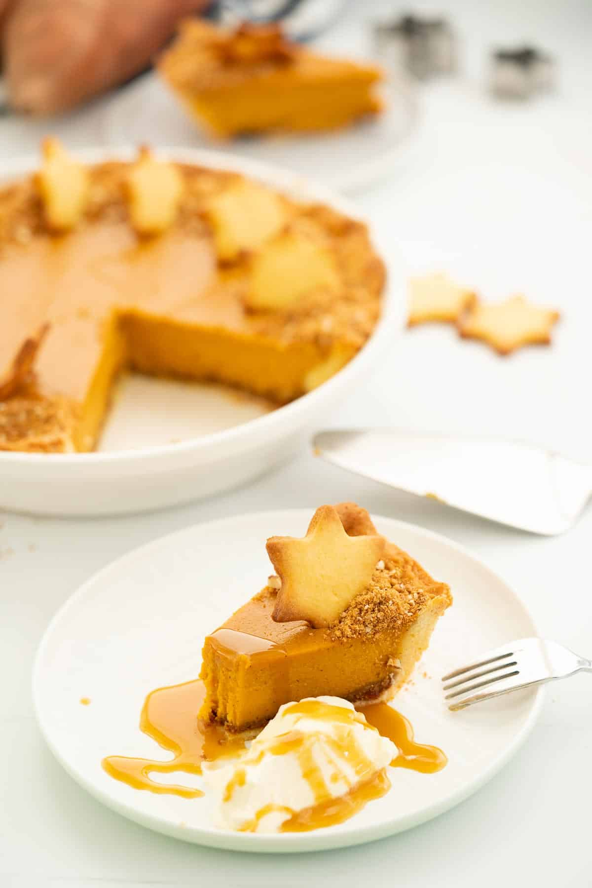 A slice of sweet potato pie decorated with a pastry star, whipped cream and caramel sauce.