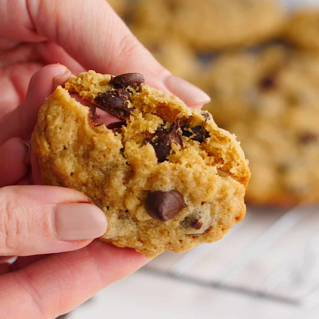 A woman's hand breaking a cookie in half to reveal oatmeal and chocolate drops.
