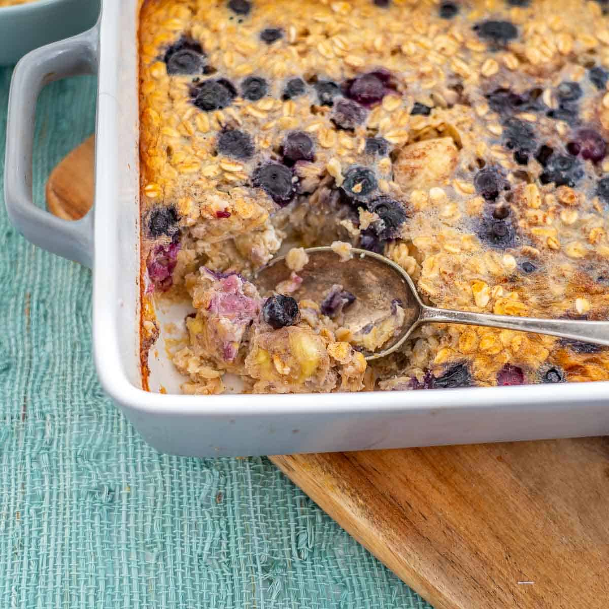 Baked oats topped with blueberries in a grey ceramic baking dish.