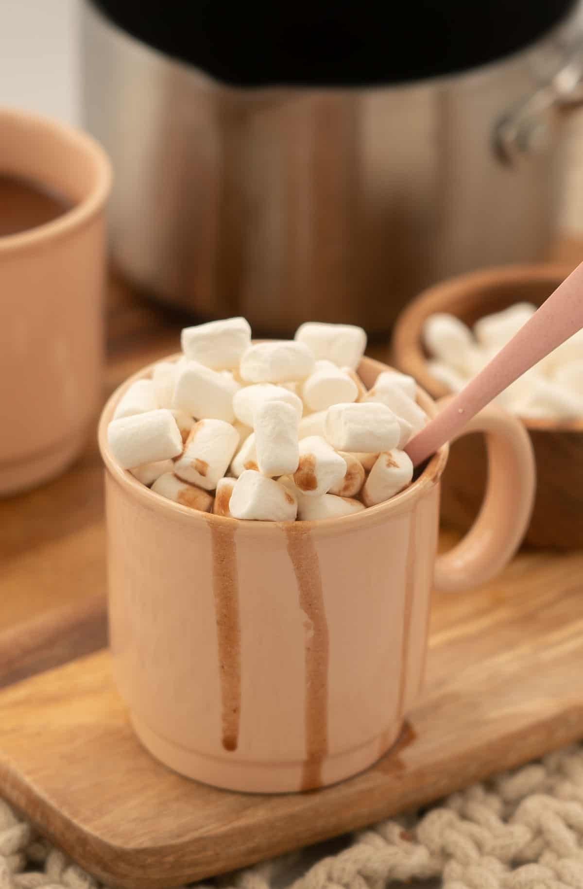 A pink mug of hot chocolate topped with mini marshmallows.