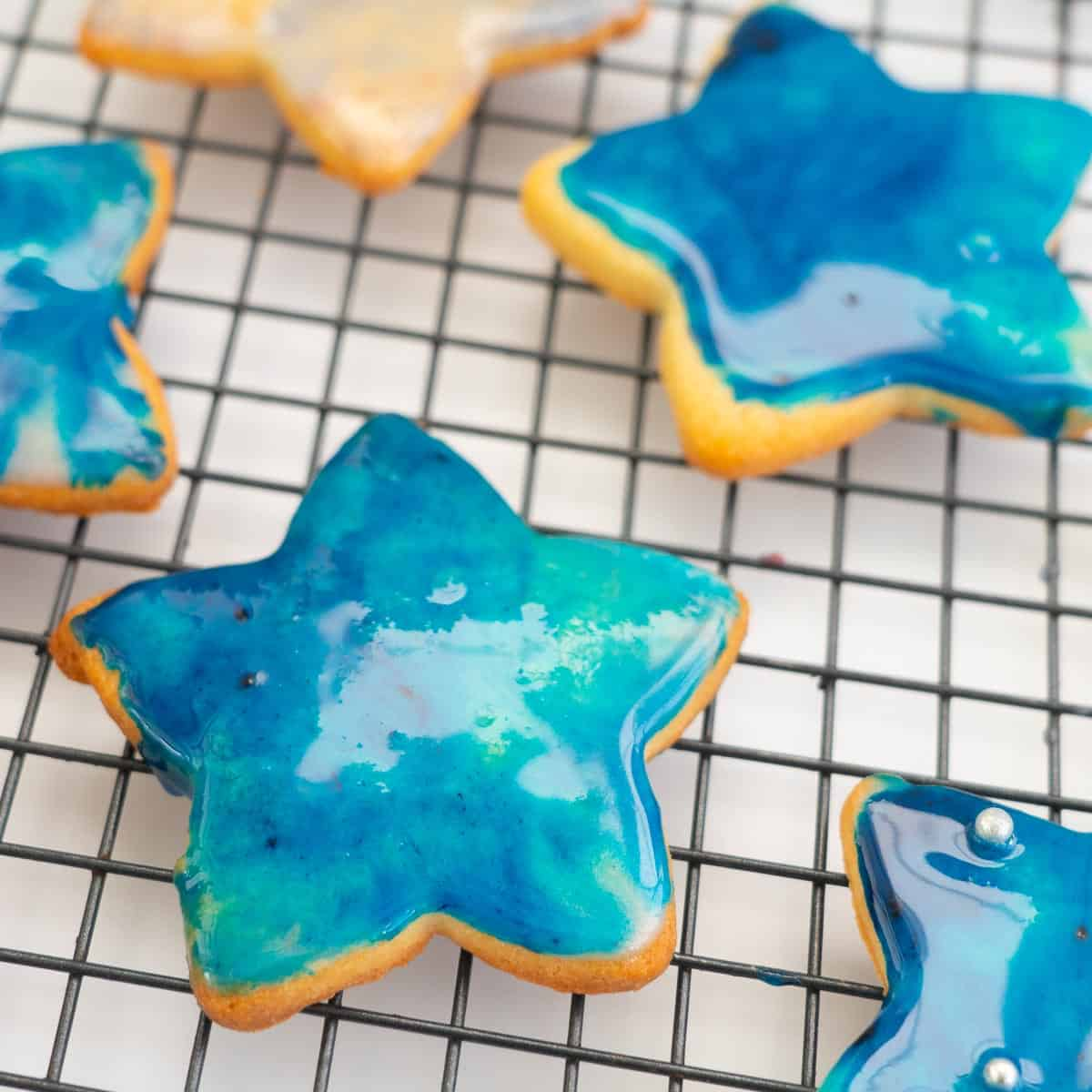 Blue galaxy iced cookies on a cooling rack.