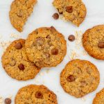 Chocolate chip oatmeal cookies lyung on white baking paper with oats and chocolate drops scattered around.
