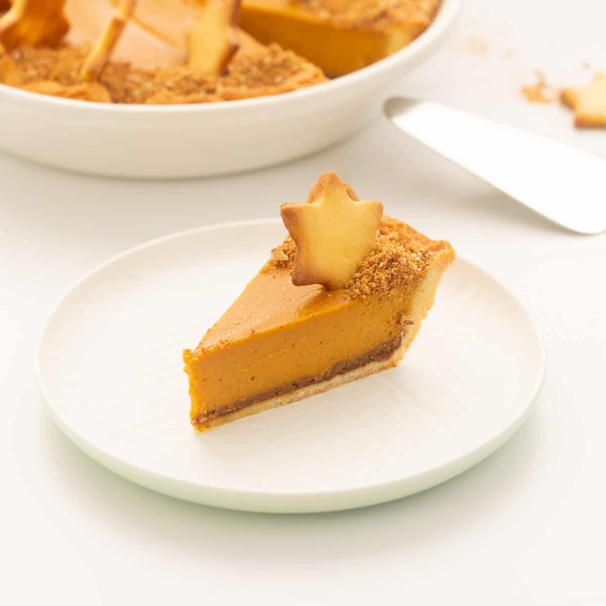 A slice of sweet potato pie decporated with a pastry star on a white plate.