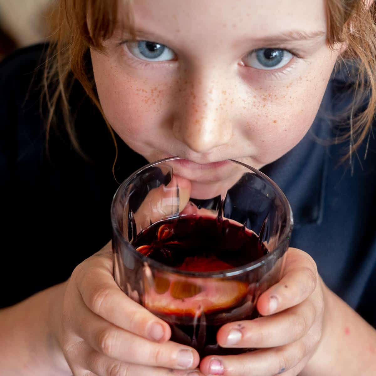 A blue eyed girl taking a sip from a glass of non-alcoholic mulled wine.