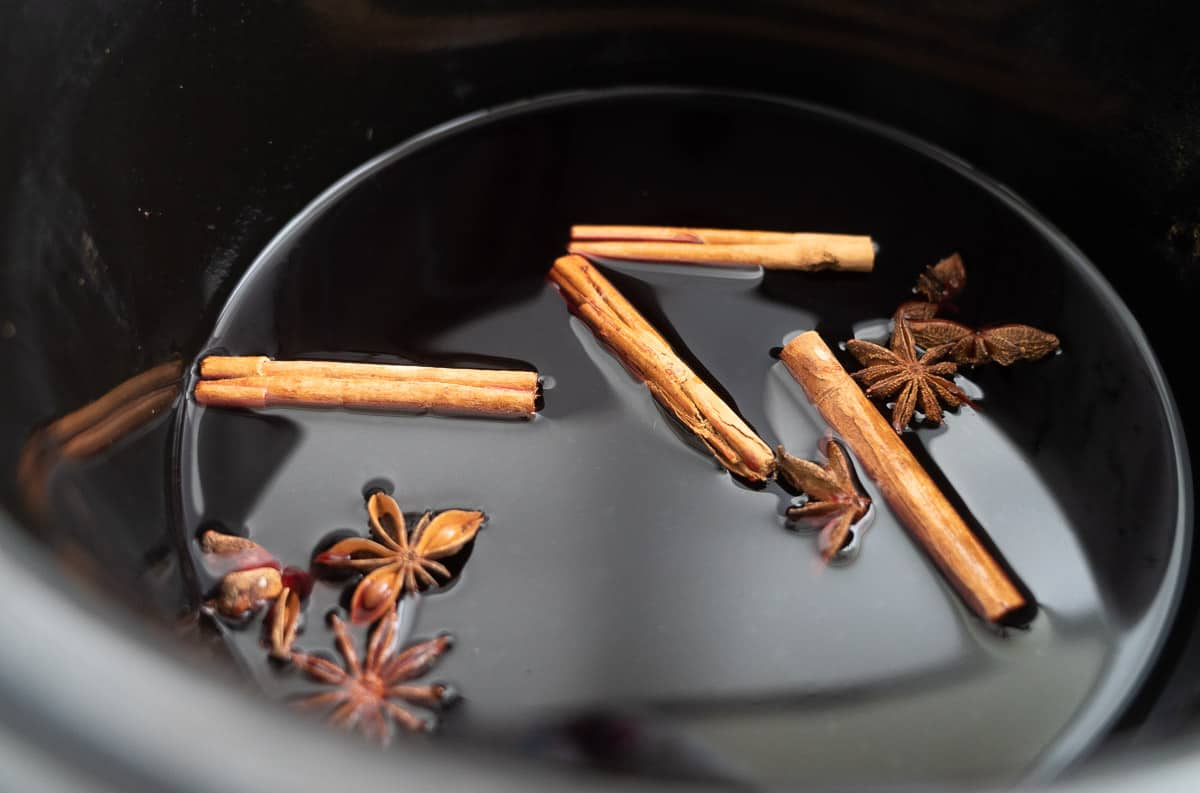 Dark grape juice in a slow cooker with cinnamon quills and star anise floating on the surface.