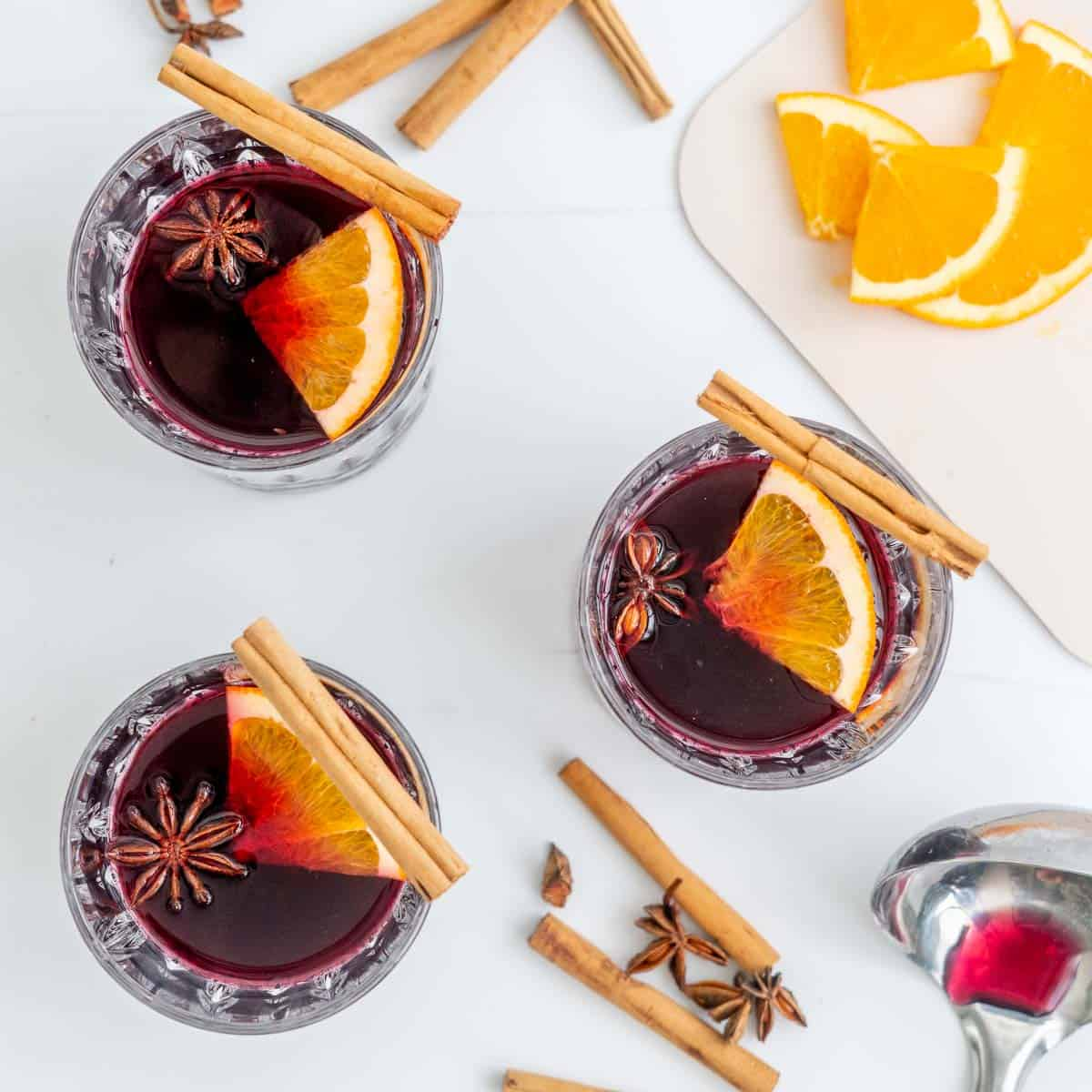 Overhead looking down at three glasses of mulled wine with orange slices, cinnamon quills and star anise.