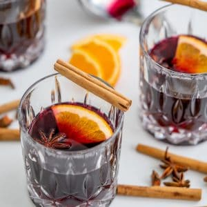 non-alcoholic mulled wine in3 cut glass tumblers, served with star anise, orange slices and cinnamon quills.