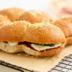 Toasted sliders filled with salami melted mozzarella and spinach leaves.