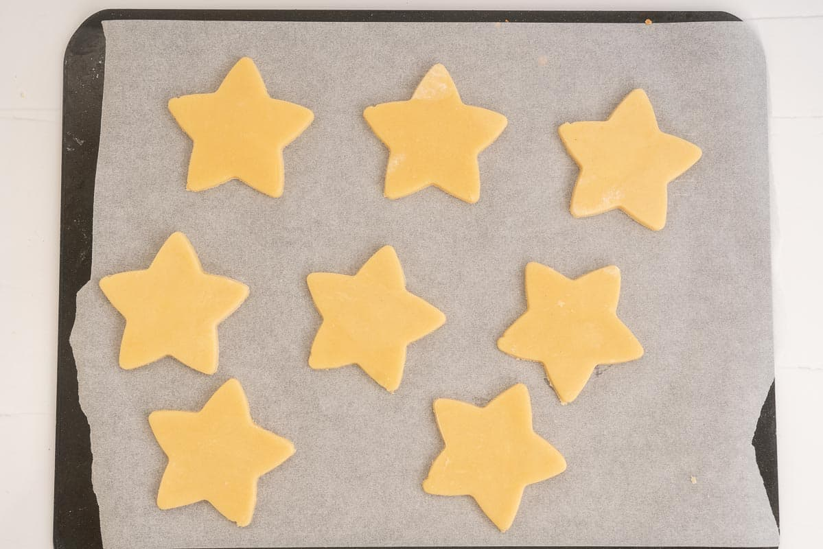star shaped cookies on a baking-paper lined tray ready to be baked.