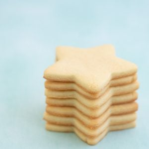Seven star shaped sugar cookies stacked in a tower on a mint green background.