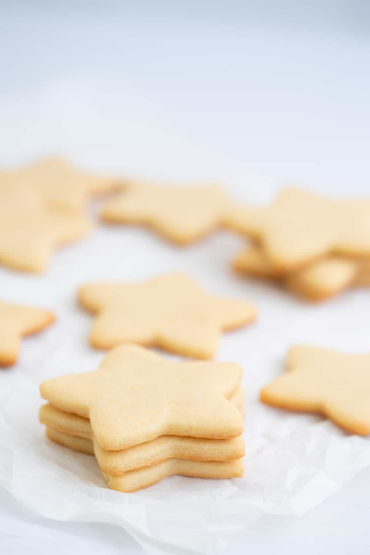 A stack of three star shaped sugar cookies on a piece of crumpled baking powder.