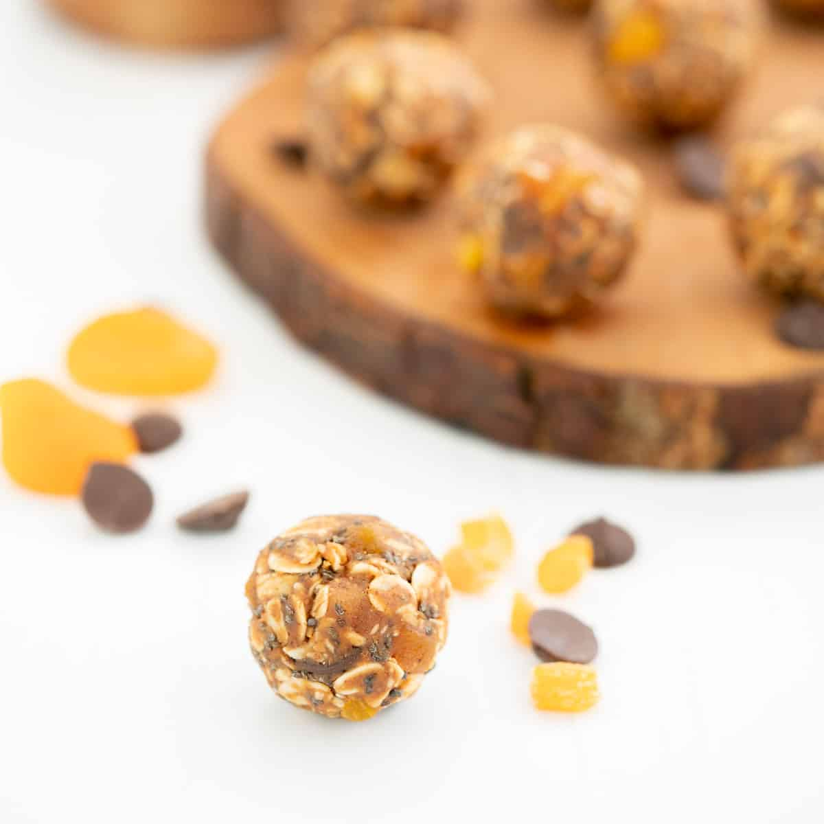 An apricot ball on a white bench top with a wooden tray of more apricot balls in the background.
