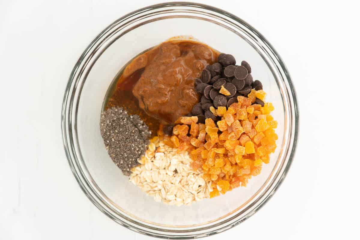 Oats, dried apricots, chia seeds, chcocoalte chips and nut butter in a mixing bowl.
