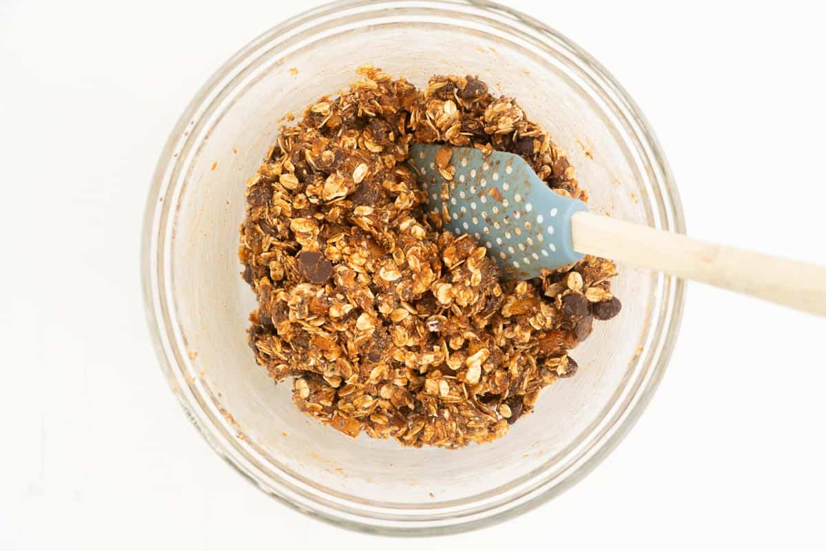 Apricot ball mix resting in a glass mixing bowl with a blue spatula.