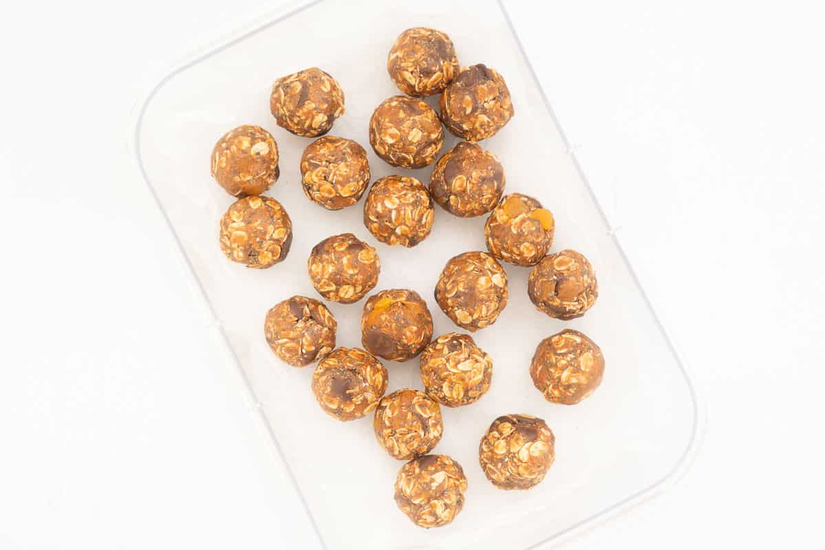 20 apricot oat balls in a container ready to refrigerate.