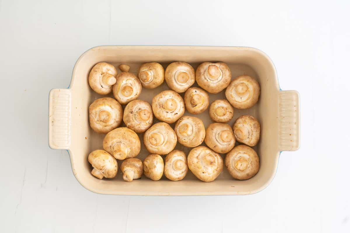 A rectangular baking dish filled with olive oil coated button mushrooms.
