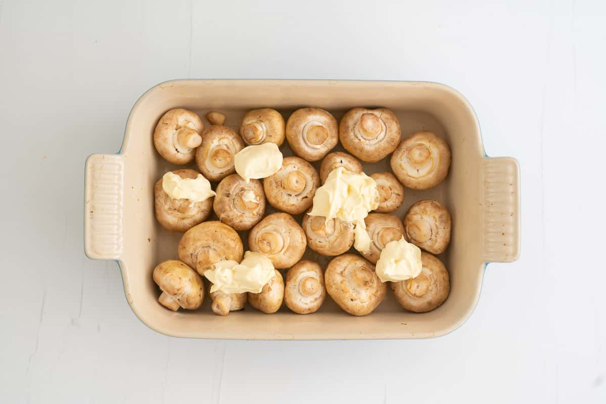 A rectangular baking dish filled with olive oil coated button mushrooms. topped with five blobs of creme fraiche.