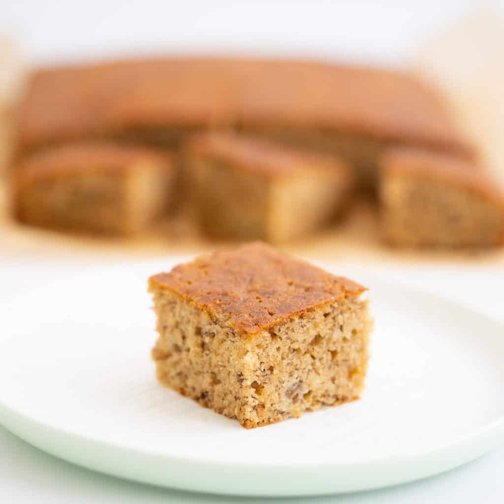 A square piece of banana cake sitting on a white plate.