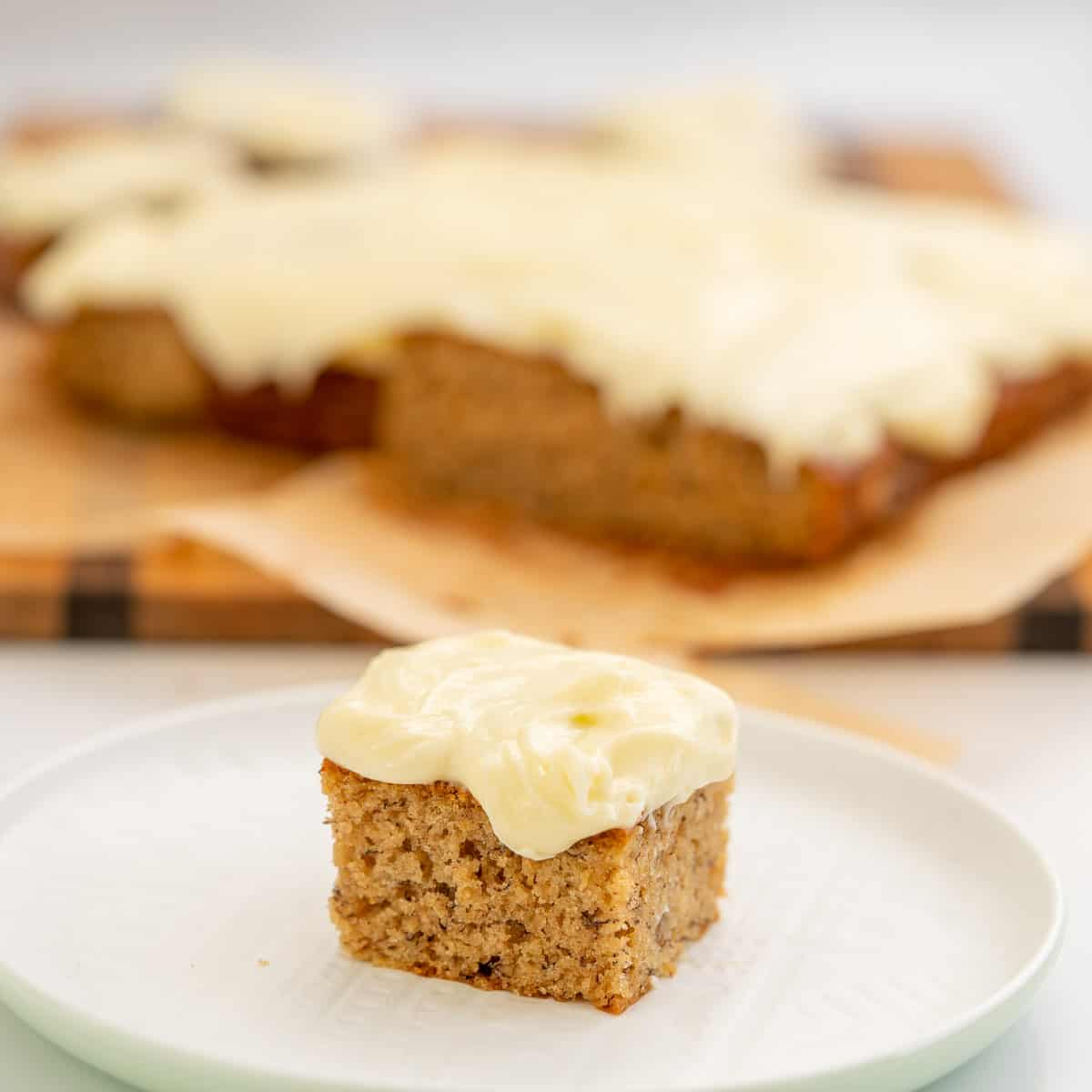 A square piece of banana cake frosted with cream cheese icing sitting on a white plate.