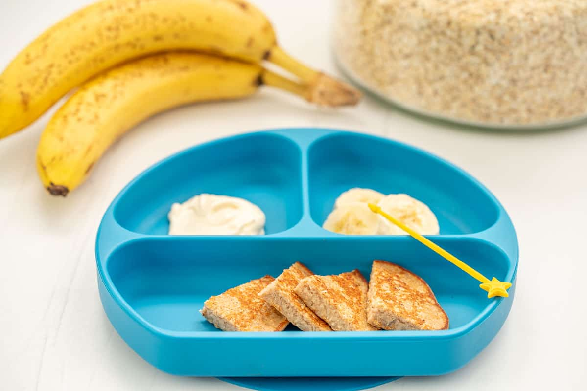Banana oat pancakes sliced into triangle wedges, on a blue baby plate with banana slices and yoghurt.
