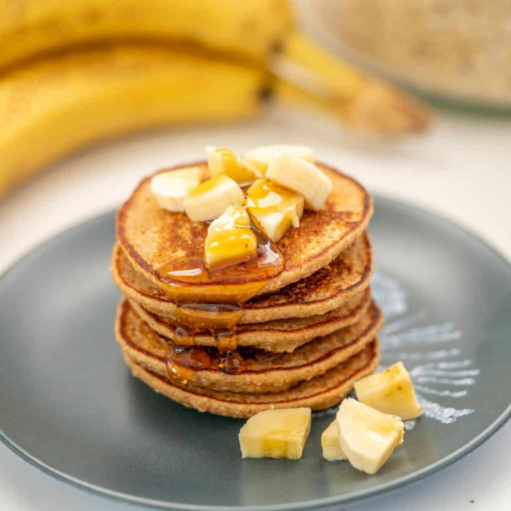 A stack of 5 pancakes on a blue plate with sliced banana and maple syrup.