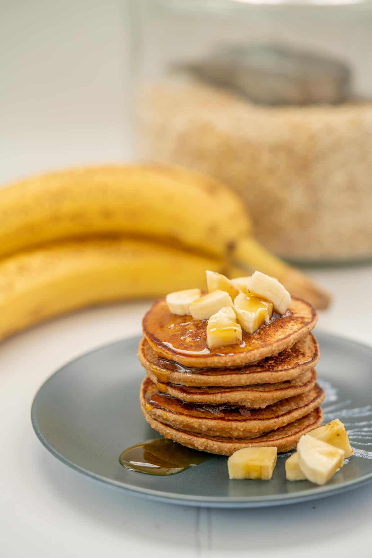 A stack of 5 pancakes on a blue plate with sliced banana and maple syrup., bananas and a jar of rolled oats in the background.