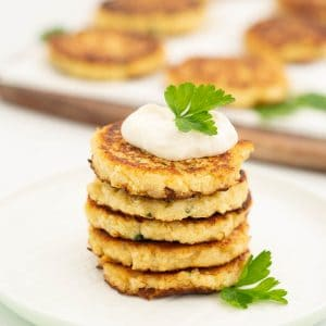 A stack of 5 cauliflower fritters topped with aioli and parsley.