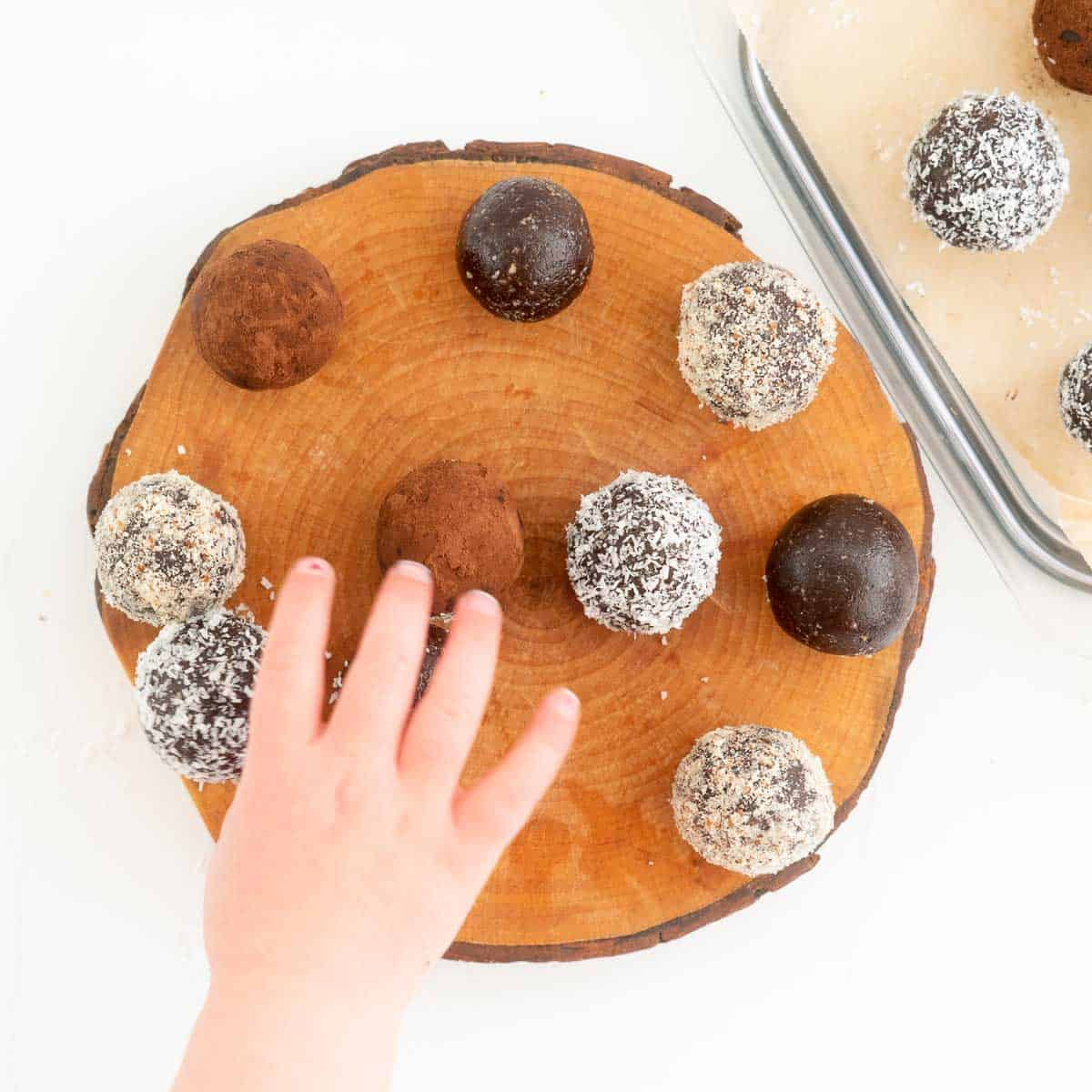 A child's hand reaching for a chocolate bliss ball.