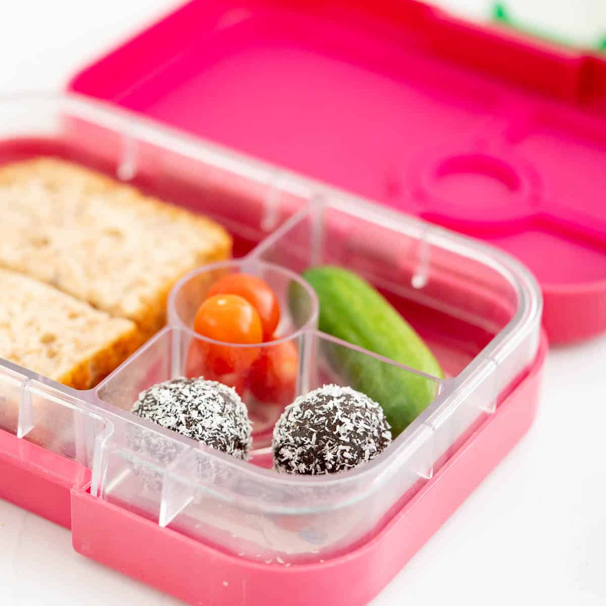A pink bento box packed with chocolate bliss balls, cucumber, tomatoes and a sandwich.