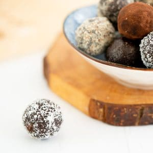 A coconut covered chocolate ball sitting on a white bench top.