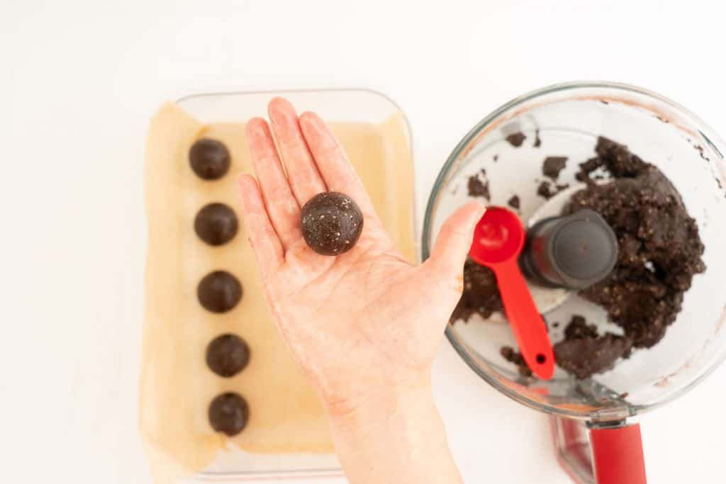 A women's hand holding a chocolate date ball above a container of date balls.