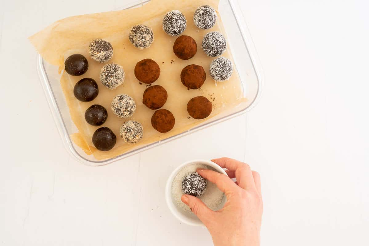 A woman's hand rolling a chocolate date ball in a bowl of desiccated coconut.