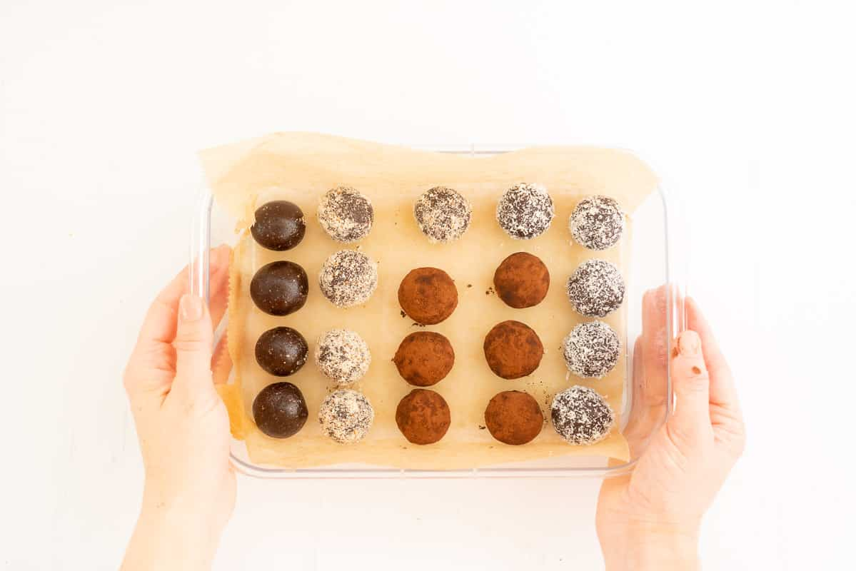 A selection of chocolate bliss balls rolled in coconut, cocoa and ground almonds in a container ready to be refrigerated.