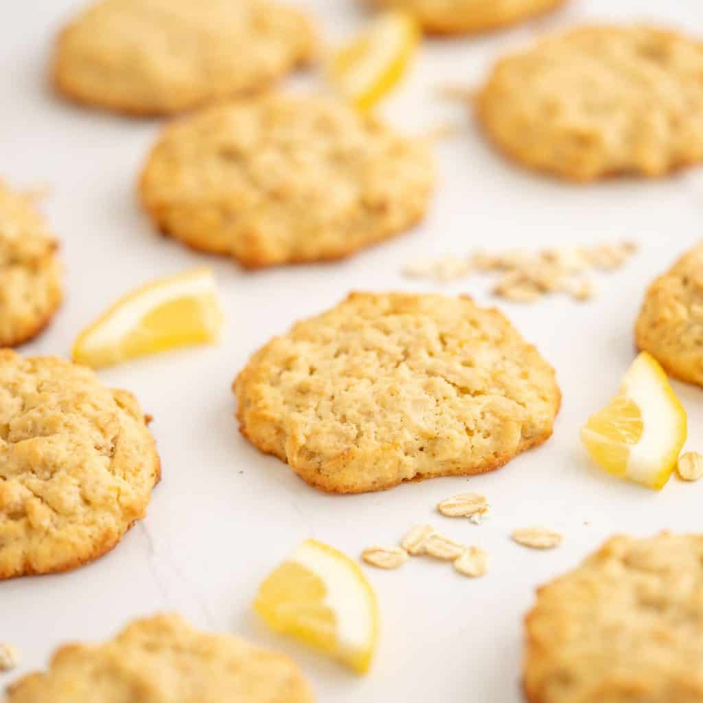 A lemon oat cookie on a white bench top with scattered rolled oats and lemon pieces.