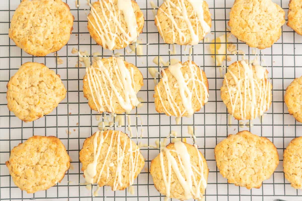 Lemon cookies on a wire cooling wrack, half drizzled with white chocolate.
