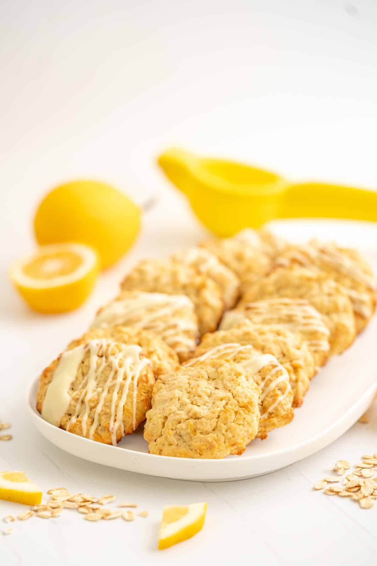 A white platter with 16 oatmeal lemon cookies, lemons and a lemon squeezer in the background.