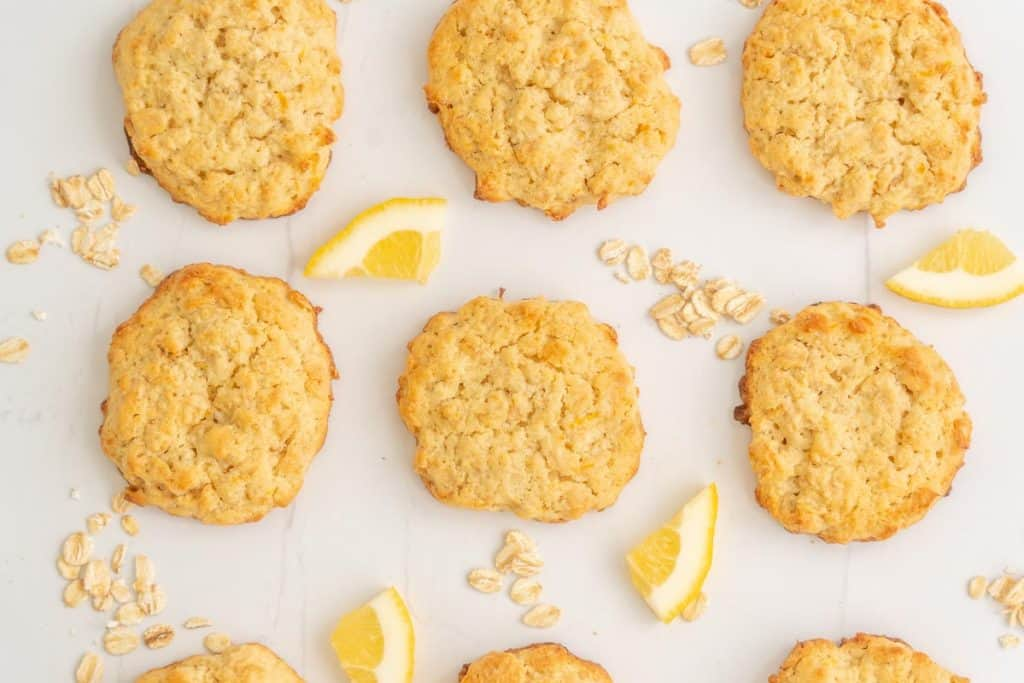 Lemon oat cookies laid out on a bench top with small pieces of lemon.
