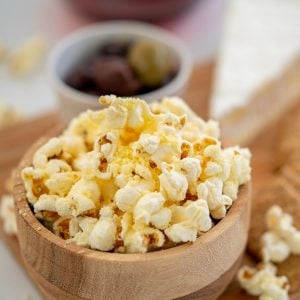 A small wooden bowl of cheese popcorn, antipasto platter ingredients in the background.