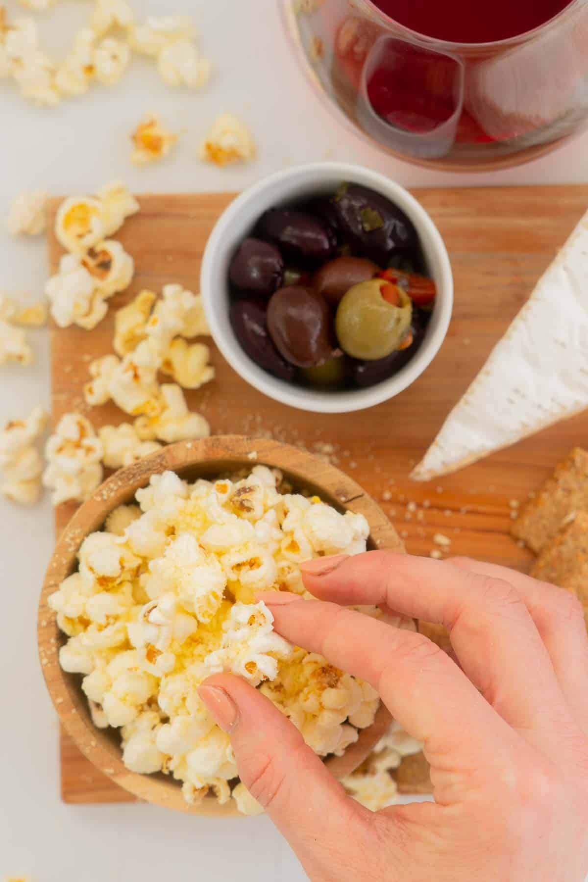 A female hand reaching for popcorn from an antipasto platter