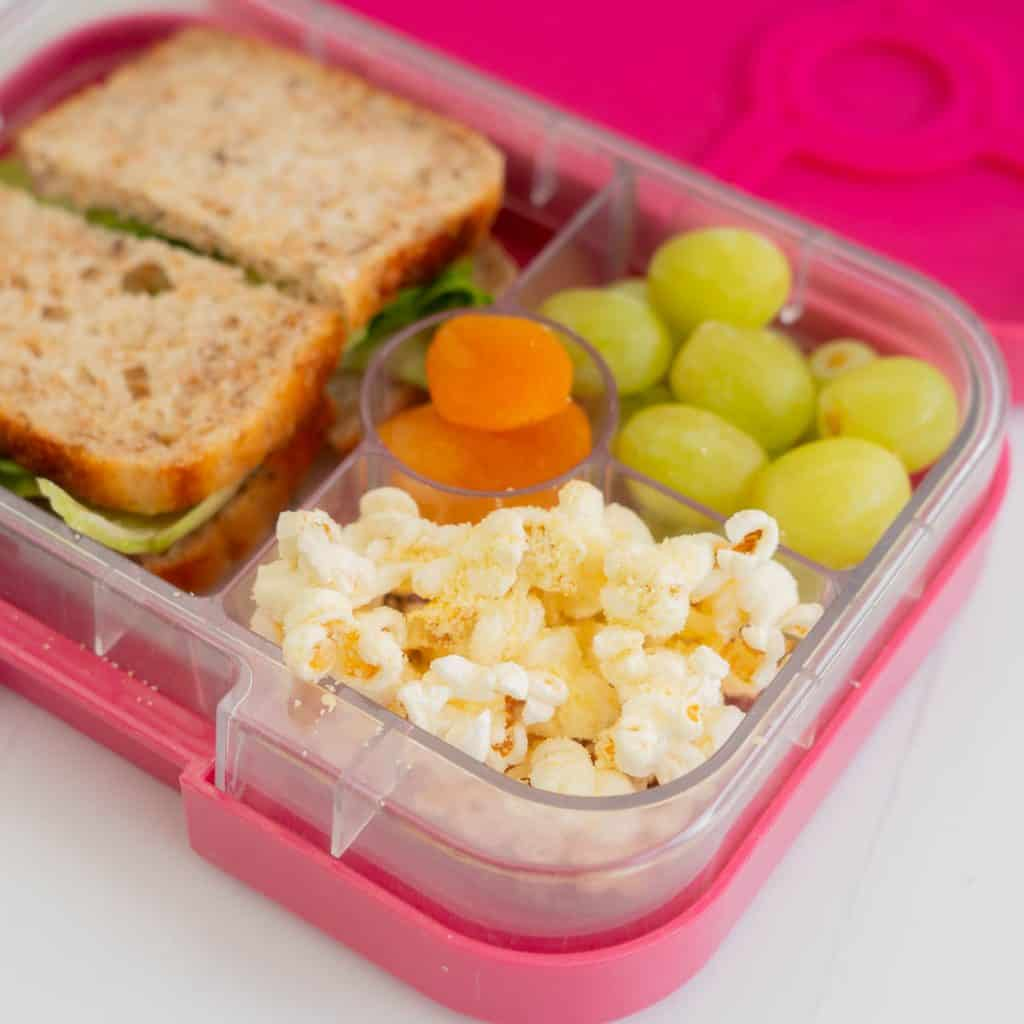 A lunchbox packed with a sandwich, fruit and popcorn.