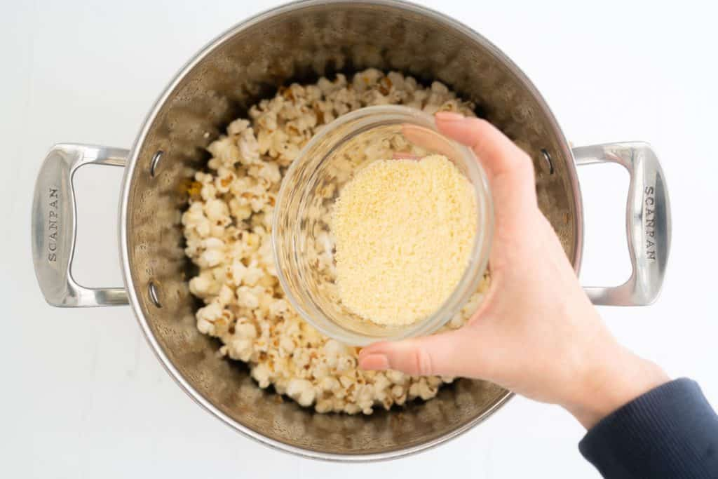 Cheese popcorn seasoning being added to a pot of popped popcorn.