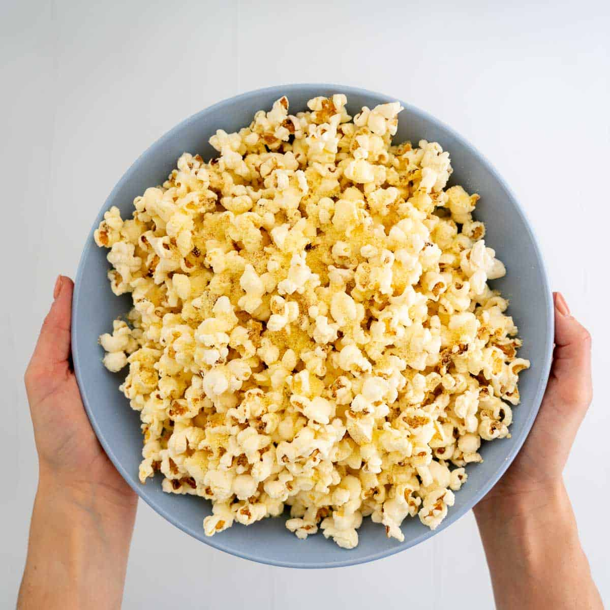 Woman's hands holding a large blue bowl filled with popcorn.
