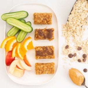 4 Peanut butter bars and chopped fruit and veggies on a white platter.