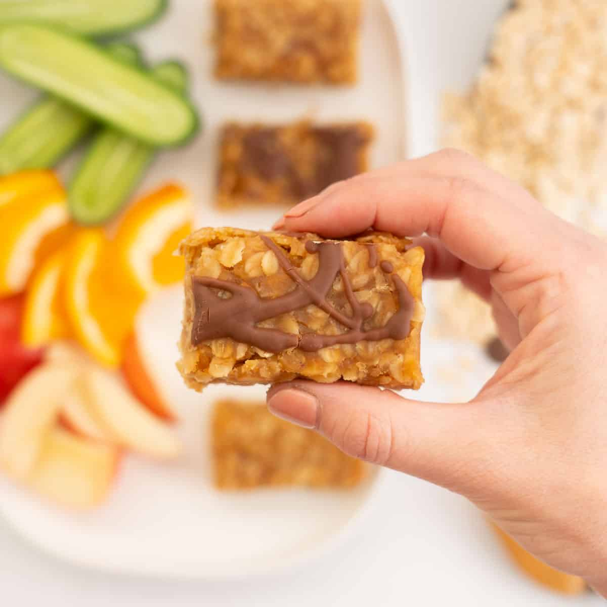 A woman's hand holding a peanut oat bar decorated with chocolate drizzle above platter of cut fruit.