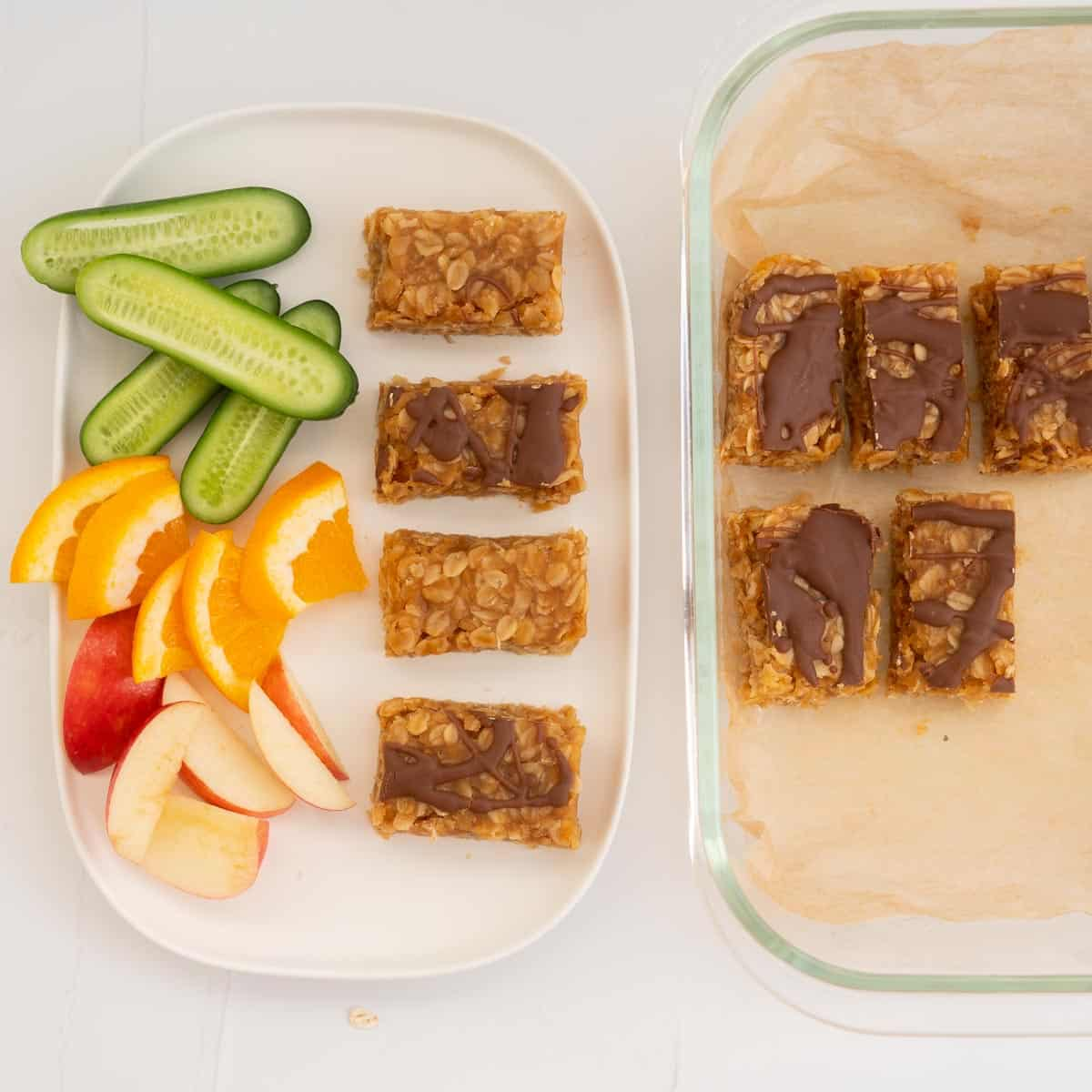 Peanut butter oat bars and fresh fruit and veggies on a white platter next to a container of bars ready to be refrigerated.