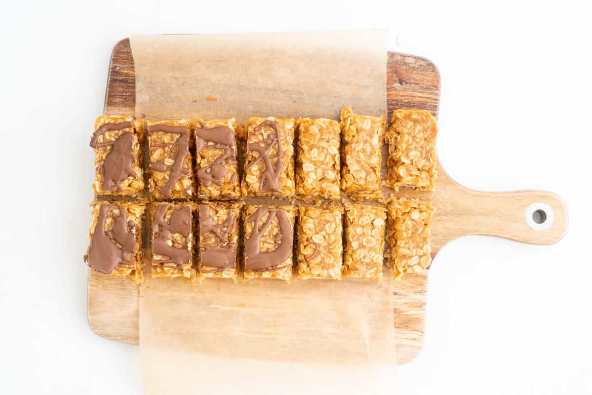 12 Peanut butter oat bars on a wooden chopping board, half drizzled with chocolate.