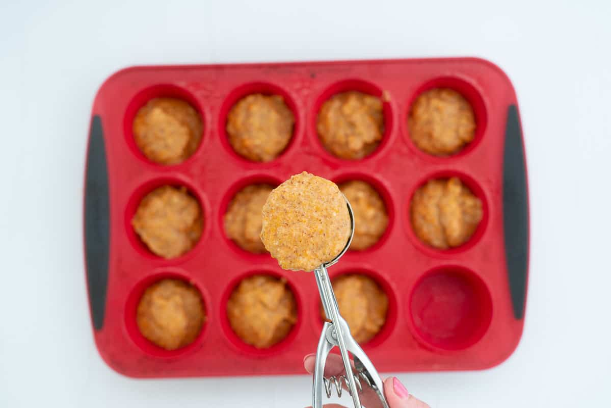 A scoop of sweet potato muffin batter being spooned into a red silicone muffin tray.